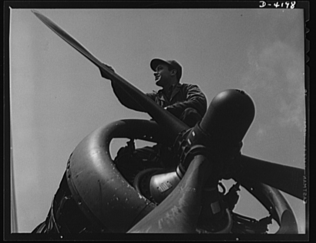 Mitchell Field. Business end of a bomber engine. The controllable pitch housing in the propeller hub assembly contains the mechanism that automatically adjusts the set of the three propellers