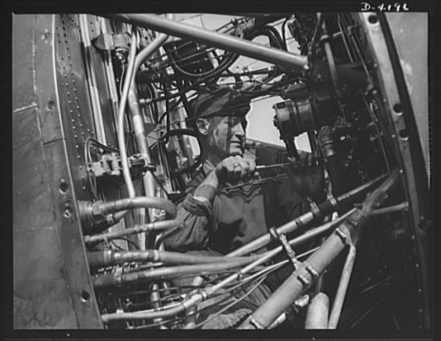 """Mitchell Field. """"Plumbing system"""" of a fighting plane. The rear end of an air-cooled aviation engine with cowling removed, showing fuel lines, ignition leads, instrument leads and other intimate portions of the anatomy of a mighty flying power plant"""