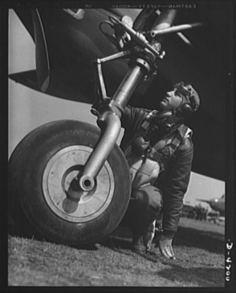 Mitchell Field. The eagle puts foot to earth. An air-crew officer dressed in full combat gear inspects a bomber landing wheel. Part of the retracting mechanism is shown