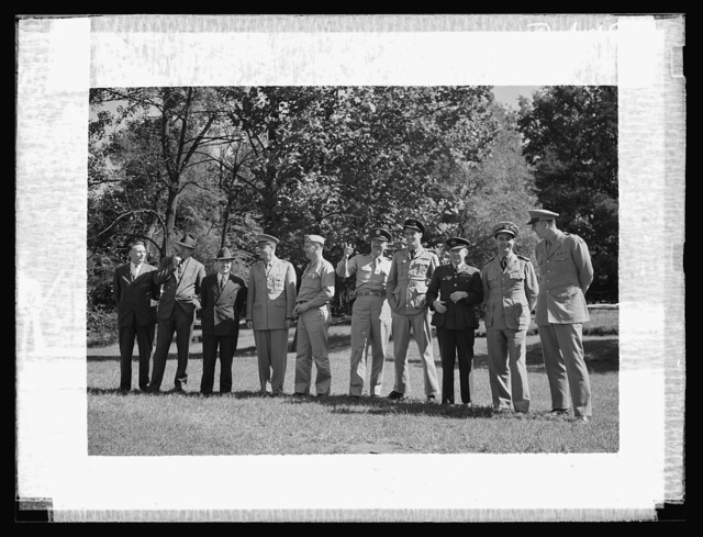 Montgomery Blair High school Victory Corps. Gold braid and official titles decorated the training field at Montgomery Blair High School in Silver Spring, Maryland, when Army, Navy, and civilian officers reviewed the Victory Corps maneuvers. Left to right: Merwin M. Peake, Chief, Pre-Induction Training Section, Civilian Personnel Division, Services of Supply, U.S.; John Lund, Executive Director, U.S. Office of Education Wartime Commission; John W. Studebaker, U.S. Commissioner of Education; Lieutenant Colonel Junius R. Smith, Executive Officer of Manpower Branch, Civilian Personnel Division, War Department; Lieutenant Colonel Harley B. West, member High School Victory Corps National Policy Committee; Major Harold W. Kent, Bureau of Public Relations, War Department; Flight Lieutenant Roald Dahl, Assistant Air Attache, British Embassy; Squadron Leader Ben Travers, Royal Air Force; Commander Harry Blaine Miller, U.S. Navy; Major Francis Parkman, member High School Victory Corps National Policy Committee