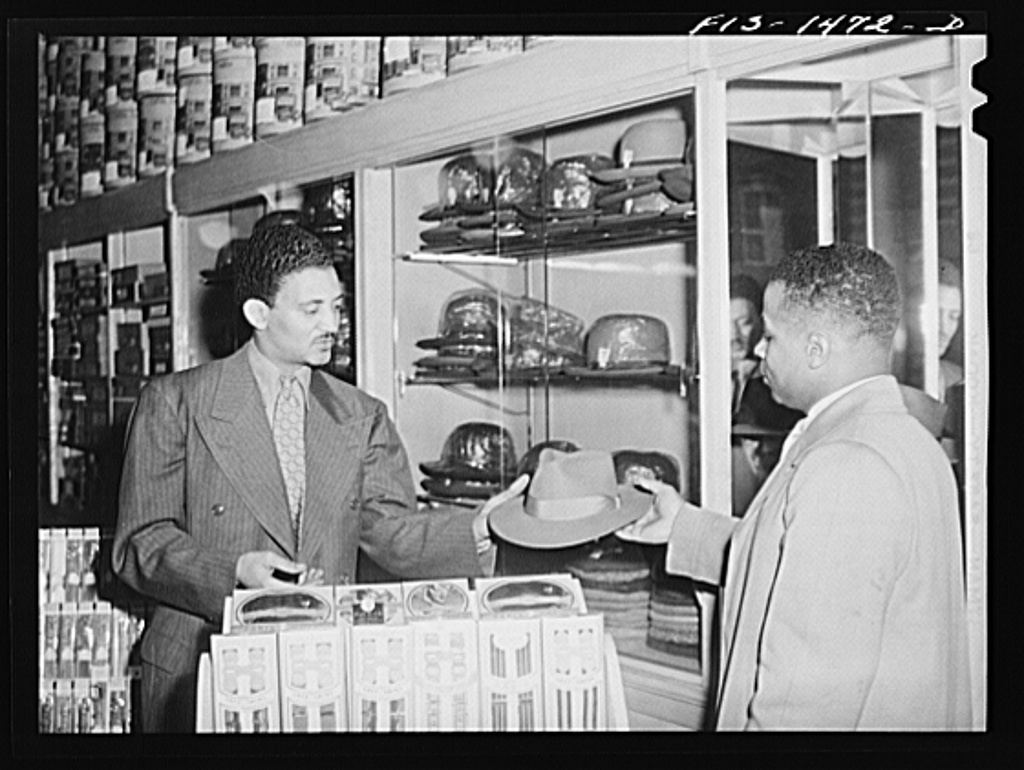 Mr. Claude Walker trying on a new hat in the Henry C. Taylor Store for Men. The salesman is Mr. William Strong, who is manager of the store. 47th Street near State Street, Chicago, Illinois