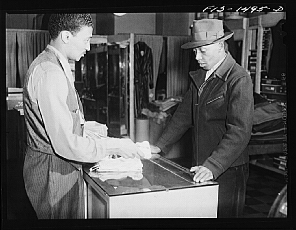 Mr. William Strong (left), manager of the Henry C. Taylor Store for Men, selling underclothes to Mr. J. Foster. 47th Street near State Street, Chicago, Illinois