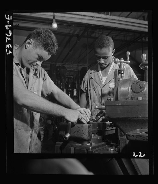 National Youth Adminstration work center (NYA), Brooklyn, New York. Two men, white and Negro, who are receiving training in machine shop practice, shown setting up shaper work to cut forty-five degree angles at base for surface gauge