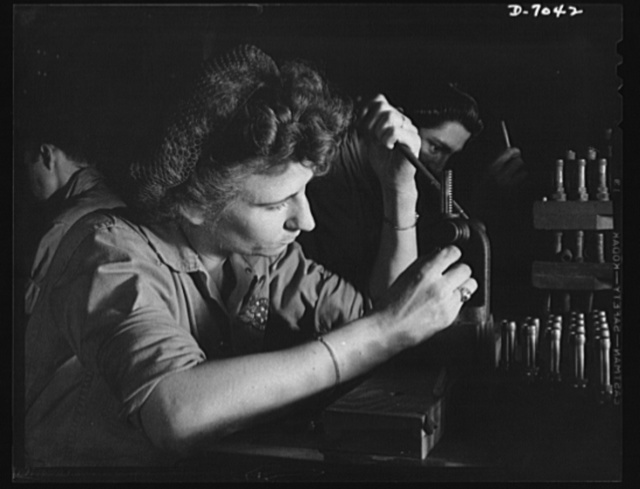 Naval air base, Corpus Christi, Texas. A Navy wife works to keep HIM flying. She has been trained to recondition spark plugs in the assembly and repair department of the Corpus Christi, Texas, naval air base. Her job is under civil service