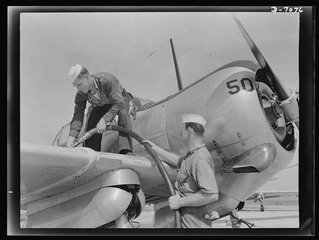 Naval air base, Corpus Christi, Texas. Feeding an SNC advanced training plane its essential supply of gasoline is done by sailor mechanics at the naval air base in Corpus Christi, Texas. Standing on the wing is Floyd Helphrey who came from Iowa to join the Navy early in the year. At right is W. Gardner of Illinois who used to be a crane operator