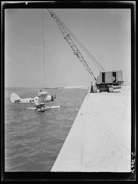 "Naval air base, Corpus Christi, Texas. Hooked to a derrick, a Navy N3N plane is made ready for hoisting out to shore onto a ""dollie."" The plane is then wheeled back to the assembly and repair department of the naval air base at Corpus Christi, Texas, for reconditioning by civil service mechanics"