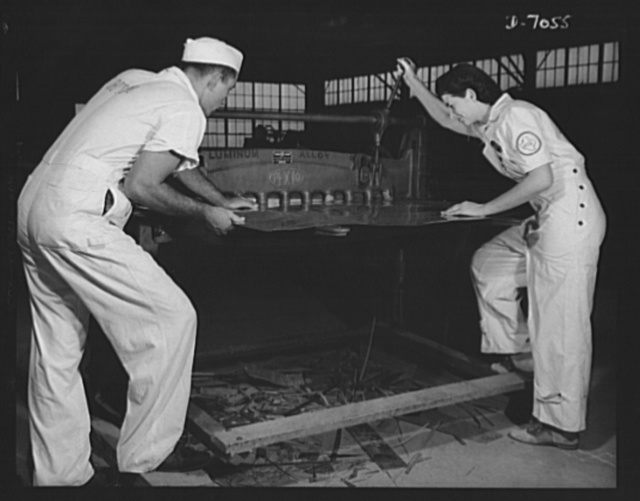 Naval air base, Corpus Christi, Texas. Learning to work a cutting machine, these two National Youth Administration (NYA) employees receive training to fit them for important work. After eight weeks, they will be eligible for civil service jobs at the naval air base in Corpus Christi, Texas