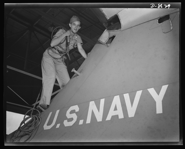 Naval air base, Corpus Christi, Texas. Mounting a navy flying ship at the naval air base in Corpus Christi, Texas, a former department store girl, is one of many women who are taking over jobs to release men for military service. She is a civil service crowler in the assembly and repair department at the base