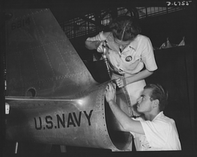 Naval air base. Corpus Christi, Texas. Mrs. Virginia Davis, a riveter in the ssembly and repair department of the naval air base in Corpus Christi, Texas, supervises Charles Potter, a National Youth Administration (NYA) trainee from Michigan. After eight of training, he will go into the civil service. Should he be inducted or enlist in the armed services, he will be valuable to mechanized units of the Army or Navy