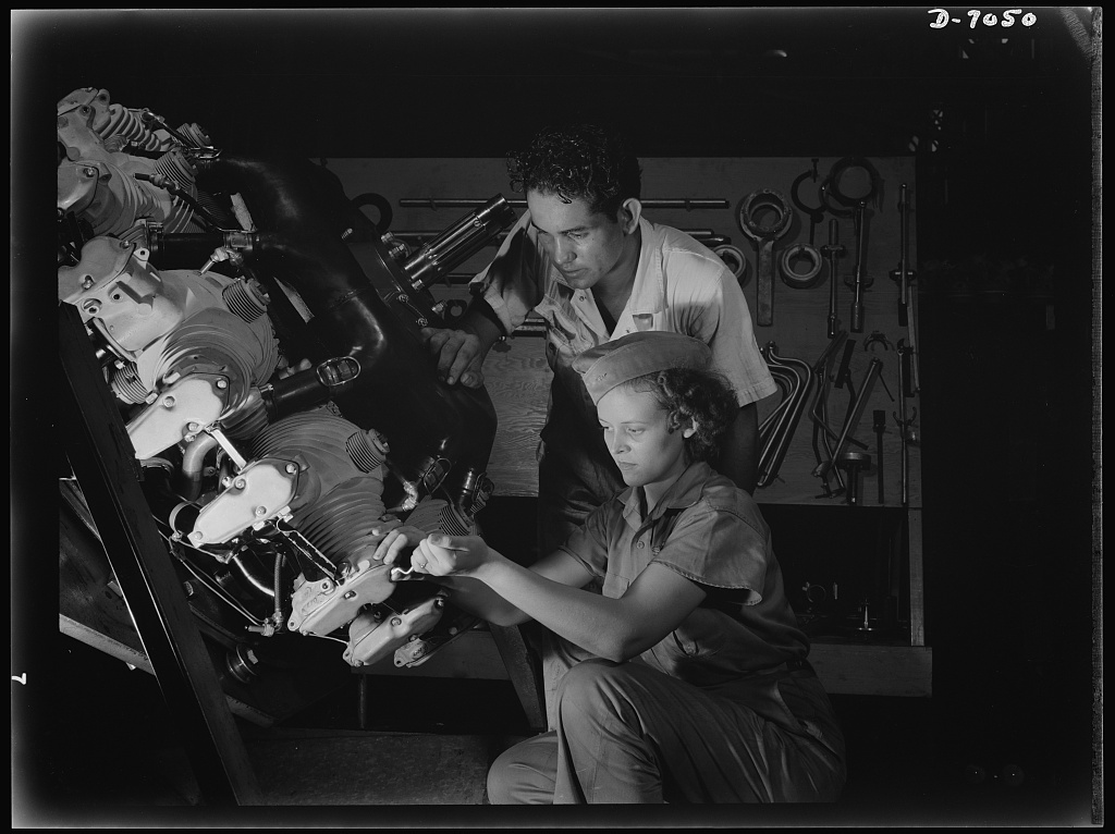 Naval air base, Corpus Christi, Texas. Now an expert mechanic, Mary Josephine Farley shows an National Youth Administration (NYA) trainee the tricks of a Wright Whirlwind Motor. He will act as her helper for about eight weeks; then he'll be qualified to work on motors for the naval air base at Corpus Christi, Texas