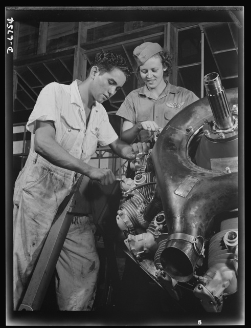 Naval air base. Corpus Christi, Texas. Now an expert mechanic, Mary Josephine Farley shows a National Youth Administration (NYA) trainee the tricks of a Wright Whirlwind motor. He will act as her helper for about eight weeks, then he'll be qualified to work on motors for the naval air base at Corpus Christi, Texas