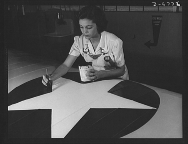 Naval air base, Corpus Christi, Texas. Painting the American insignia on airplane wings is a job that Mrs. Irma Lee McElroy, a former office worker, does with precision and patriotic zeal. Mrs. McElroy is a civil service employee at the naval air base in Corpus Christi, Texas. Her husband is a flight instructor