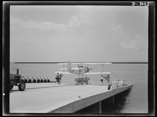 Naval air base, Corpus Christi, Texas. Ready to soar out over the water, this N3N training plane coasts down the plank to launching. Cadets at the naval air base in Corpus Christi, Texas, are trained in planes carefully conditioned by sailor mechanics at the base