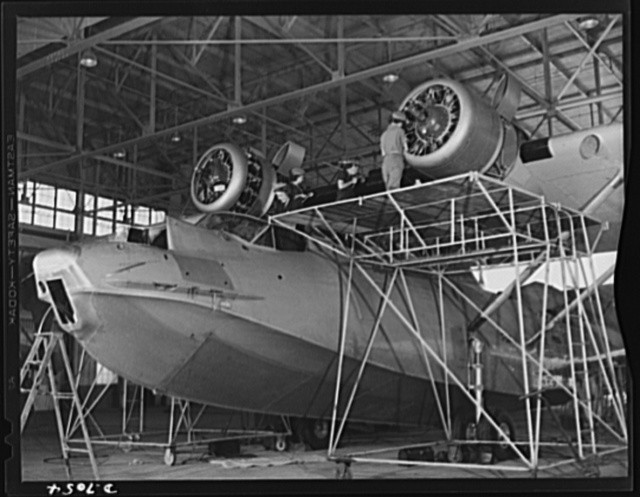 Naval air base, Corpus Christi, Texas. The pilots fly it, but the ground crew keeps it flying. Every ship, after so many hours in the air must be completely reconditioned. Here, in a hanger of the naval air base at Corpus Christi, Texas, women Civil Service workers of the assembly and repair department are trained to check carefully every part of the plane. Service of a Navy PBY ship
