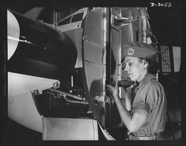 Naval air base, Corpus Christi, Texas. There's a war to be won, and Miss Mildred Hanna is helping to win it. After Pearl Harbor, Miss Hanna left school teaching and went to the ssembly and repair department of the naval air base at Corpus Christi, Texas. Here she is working on the firewall of a PBY plane. She is a civil service worker at the base