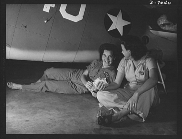 "Naval air base, Corpus  Christi, Texas. War-time luncheon ""under the shade of ....a Navy plane. These women workers held man-size jobs in the Assembly and Repair Department at the Corpus Christi, Texas, naval air base. Slack suits and coveralls take the place of afternoon frocks for these workers"