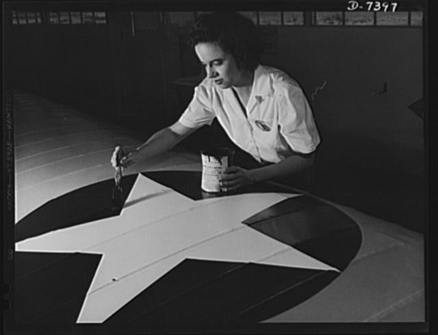 Naval air base, Corpus Christi, Texas. Women from all fields have joined the production army. Miss Grace Weaver, a civil service worker at the Corpus Christi  naval air base and a school teacher before the war, is doing her part for Victory along with her brother who is a flying instructor in the Army. Miss Weaver paints the American insignia on repaired Navy plane wings