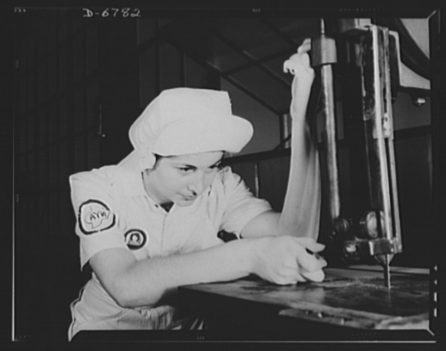 "Naval air base. Corpus Christi, Texas. ""Women in white"" doctor Navy airplane motors at the Corpus Christi, Texas, naval air base. Mildred Webb, a National Youth Administration (NYA) trainee at the base is learning to operate a cutting machine in the Assembly and Repair Department. After about eight weeks as an apprentice she will be eligible for a civil service job in the capacity for which she has been trained"