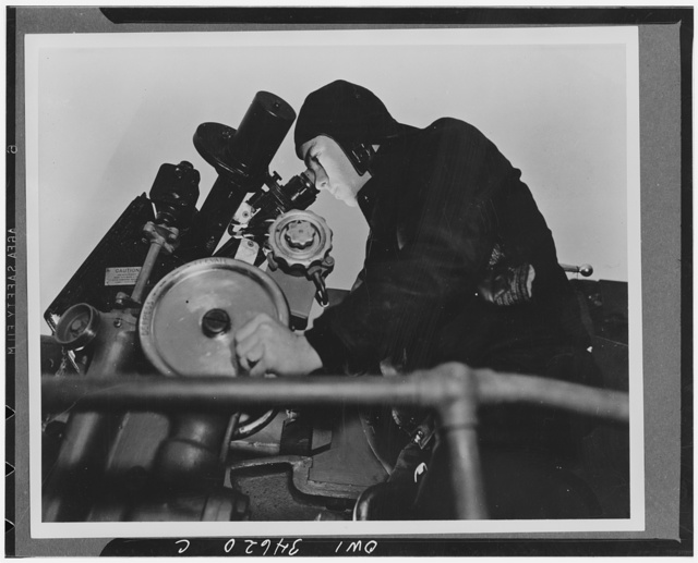 Navy armed guard sighting in practice the five-inch rifle of a Liberty ship in convoy at sea