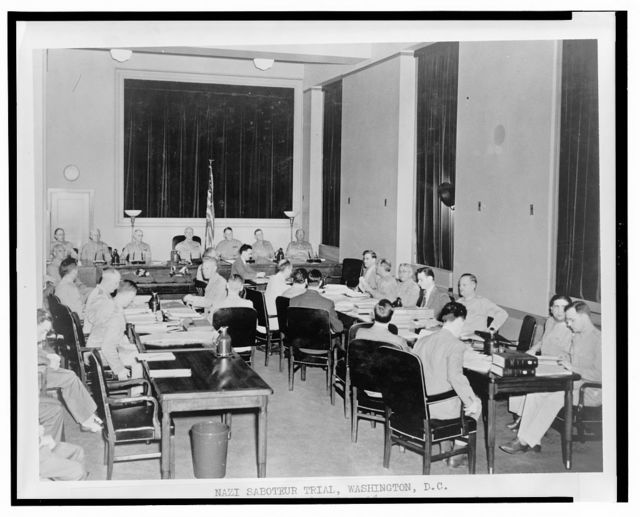 Nazi saboteur trial, Washington, D.C. The special seven-man military commission opens the third day of its proceedings in the trial of eight Nazi saboteurs in the fifth floor courtroom of the Department of Justice building. Sitting on the commission left to right are: Brigadier General John T. Lewis; Major General Lorenzo D. Casser; Major General Walter S. Grant; Major General Frank R. McCoy, president of the commission; Major General Blanton Winship; Brigadier General Guy V. Henry; Brigadier General John T. Kennedy