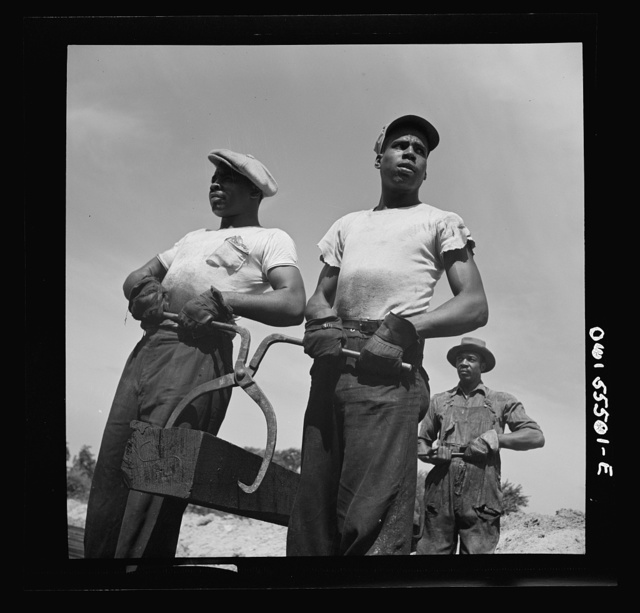 Negro laborers carrying and laying railroad ties for a spur line into a coal storage space for the federal government