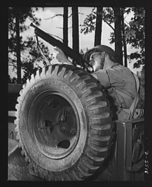 New River, North Carolina. Marine truck convoy. When a leatherneck gets a tommy gun lined up, something is due to be hit. Bulwarked by a spare tire, this capable member of a Marine Corps truck convoy goes in for a little practice with a submachine gun as his column halts on a training cruise near New River, North Carolina