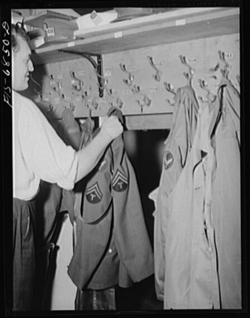 New York, New York. Actor hanging up coats in the coat room at the Stage Door canteen