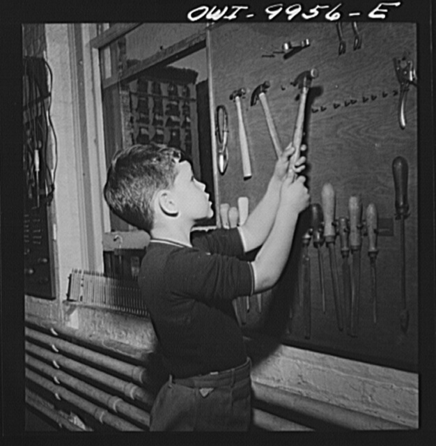 New York, New York. Children's Colony, a school for refugee children administered by a Viennese. British refugee child putting tools away