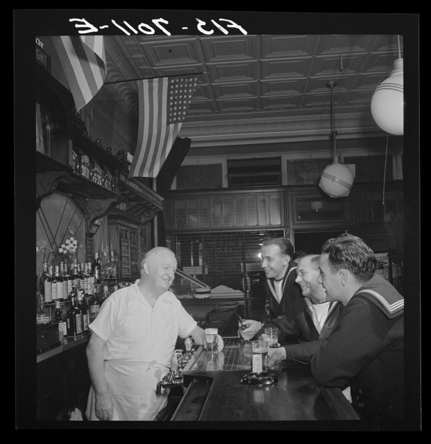 """New York, New York. Irish-American bartender serving beer to British sailors in a Third Avenue bar in the """"Forties"""""""