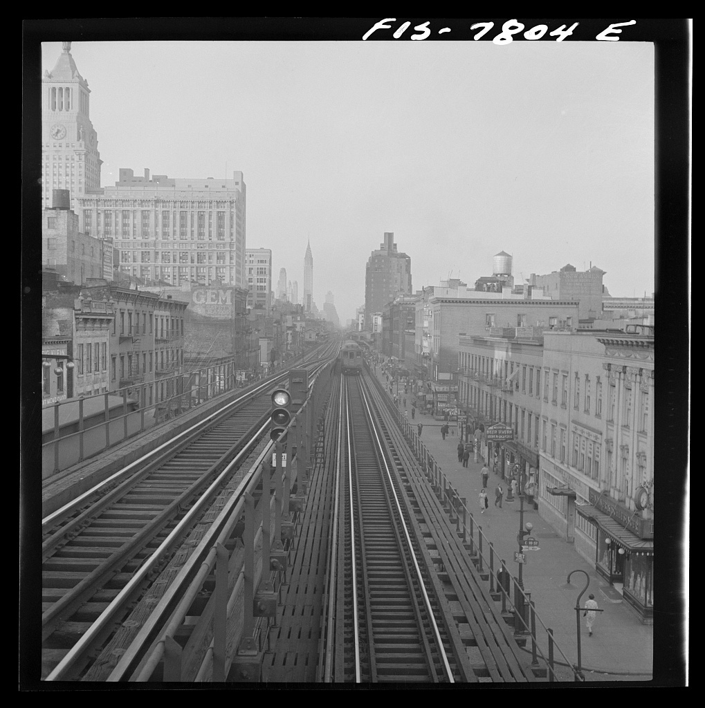 New York, New York. Looking north from the Ninth Street station on the Third Avenue elevated railway as a train leaves on the local track