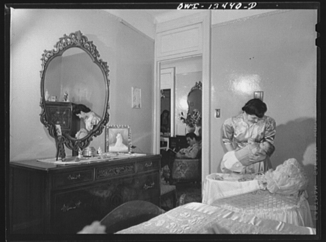 New York, New York. Mrs. Frank Romano putting her baby to bed. Her husband works in the Brooklyn Navy Yard