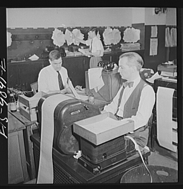 New York, New York. New York Times newspaper syndicate. Correspondents of American newspapers which are syndicate members. In background, copy boy posts Times dispatches