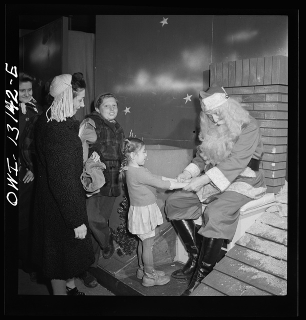 New York, New York. R. H. Macy and Company department store during the week before Christmas. Children line up to talk with Santa Claus. They are two Santas, concealed from one another by a labyrinth to prevent disillusionment of the children. Each child is presented with candy and tells Santa his or her desires