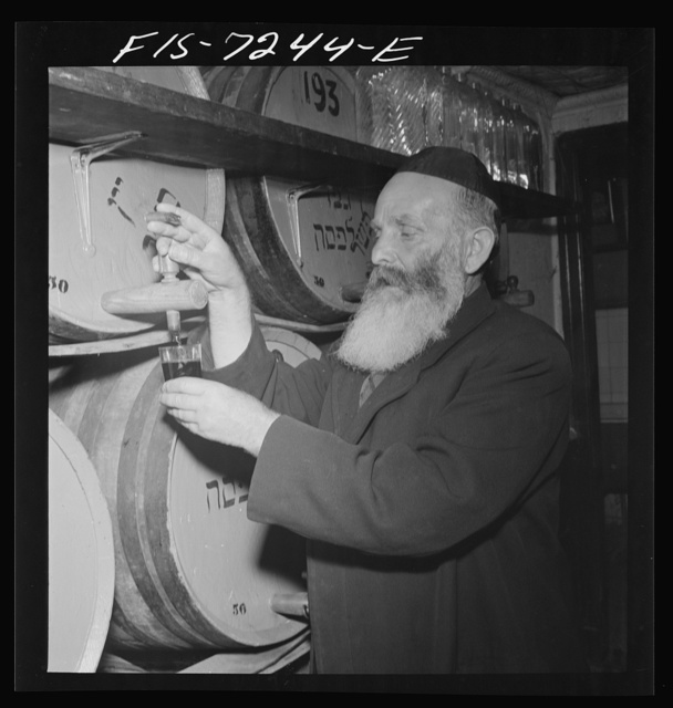 New York, New York. Rabbi in a kosher wine shop in the New York's Jewish section. His job is to inspect wines to see that they are made in the kosher manner. He also sells his services as an after-dinner speaker at Jewish functions all over the country; he speaks practically no English, only Yiddish
