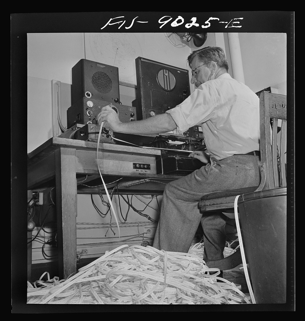 New York, New York. Radio room of the New York Times newspaper. The Times listening post, between 10 and 12 PM, between first and second editions. The operator is listening to Axis news (propaganda) broadcast. Paper in foreground has been previously examined to see what has already been covered in last edition of paper. Operator reports any new angles to city editor. Messages are recorded in tape in international Morse code