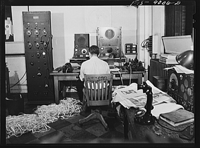 New York, New York. Radio room of the New York Times newspaper. The Times listening post, between 10 and 12 PM, between first and second editions. The operator is listening to Axis news (propaganda) broadcast. Paper in foreground has been previously examined to see what has already been covered in last edition of paper. Operator reports and new angles to city editor. Messages are recorded on tape in international Morse code