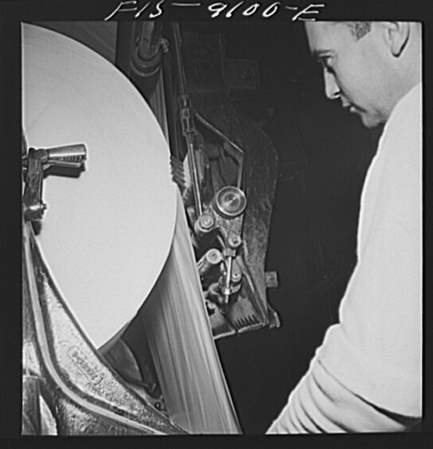 New York, New York. Reel room of the New York Times newspaper. In threading paper through presses two roles are pasted together by automatic paster so that presses never stop running