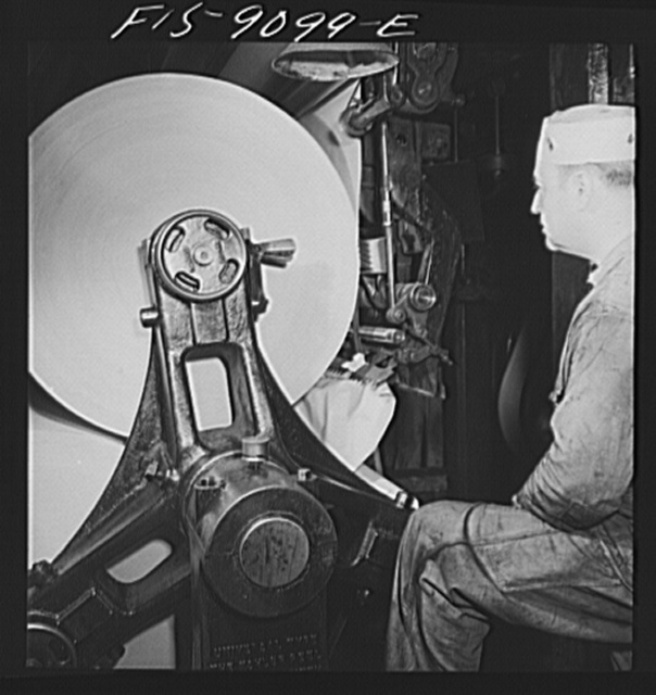 New York, New York. Reel room of the New York Times newspaper. In threading paper through presses, two rolls of paper are pasted together by automatic paster so that presses never stop moving