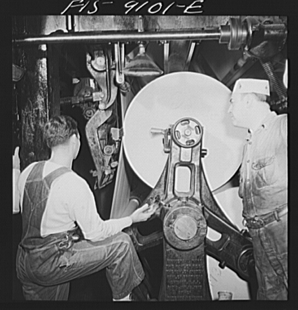 New York, New York. Reel room of the New York Times newspaper. In threading paper through presses two rolls of paper are pasted together by automatic paster so that presses never stop moving