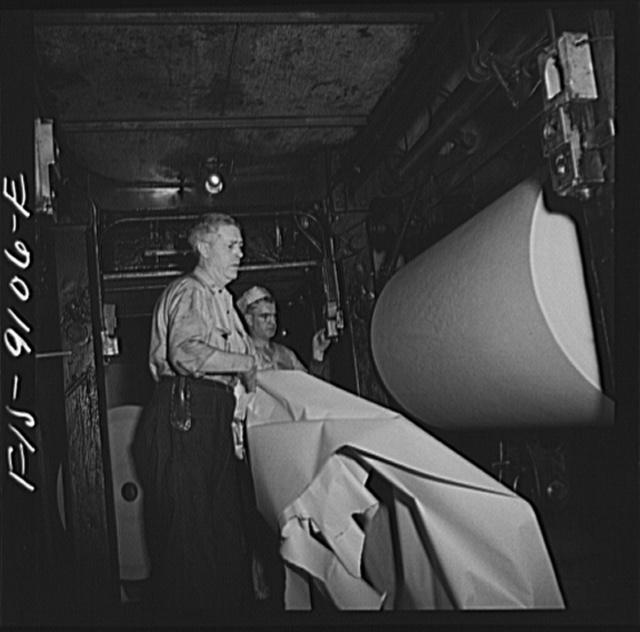 New York, New York. Reel room of the New York Times newspaper. Preparing to thread paper through presses