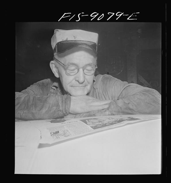 New York, New York. Reel room of the New York Times newspaper. Pressman resting between editions