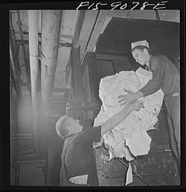 """New York, New York. Reel room of the New York Times newspaper. Waste paper is picked up off floor, placed in bins, baled and sold to the government for scrap. This young boy is an apprentice, or """"fly boy"""""""