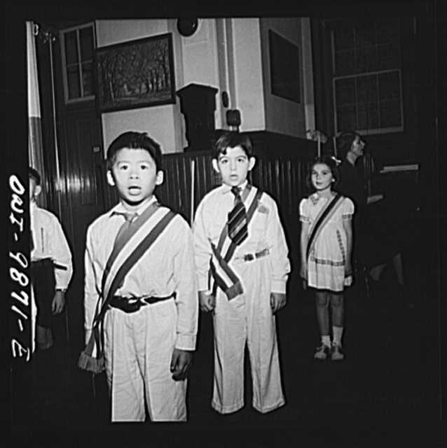 New York, New York. Students singing the Star Spangled Banner in a public school at Seventy-first Street and First Avenue, at Columbus Day assembly. Janet Winn [or Wynn], a Czech-American child, a member of the color guard, is in the background