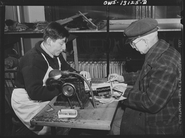 New York, New York. The War Emergency Board of the fur industry formed a fur vest project. Various fur factories donate the services of their employees one day a week to make fur-lined vests for the merchant marine. Expressman who has just brought in a new shipment of fur coats, going over receipts with a worker