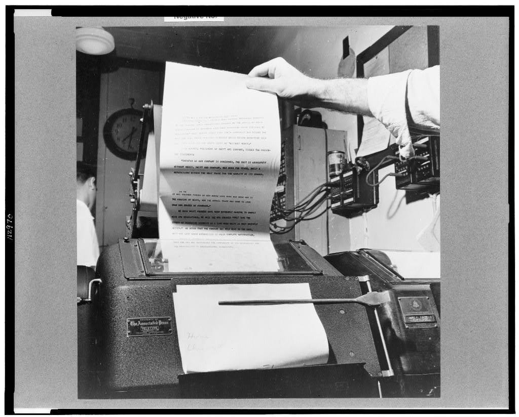 New York, New York. Wire room of the New York Times newspaper. Copy boy about to tear off dispatch coming over Associated Press