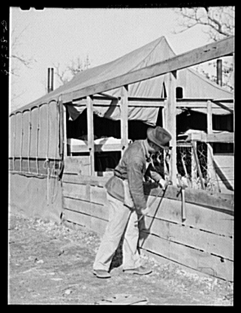 Newton County, Missouri. Camp Crowder area. Farmer who spent the winter as a carpenter, dismantling the roadside accomodations he built for himself and family, prepares to go back to the farm