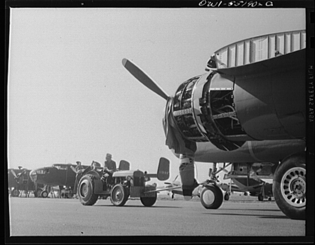 North American B-25 bombers are moved to their position on the flight ramp by a small tractor