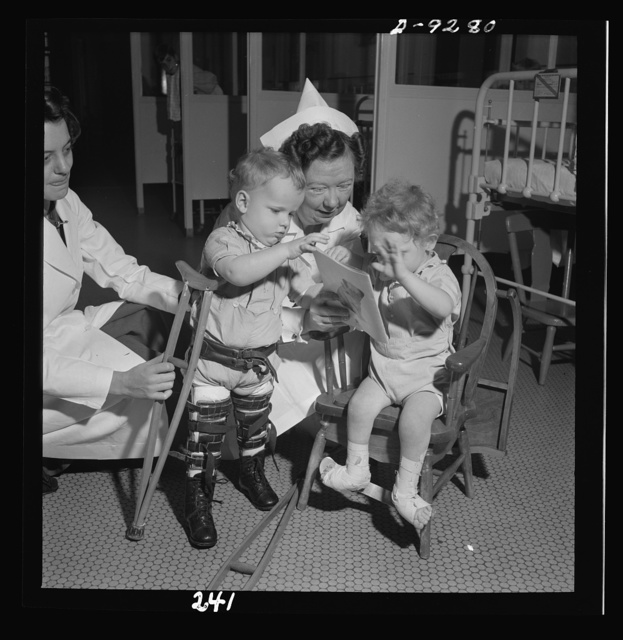 Nurse training. A nurse and the physical therapist negotiate something of a dispute over a picture book between two young patients in an orthopedic hospital