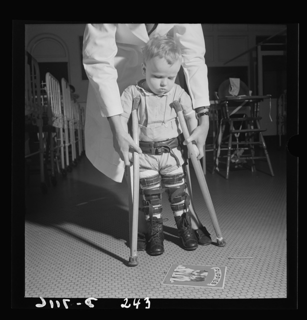 Nurse training. A student nurse, acting as physical therapist, points to the picture book, thus encouraging this toddler to learn to use his crutches