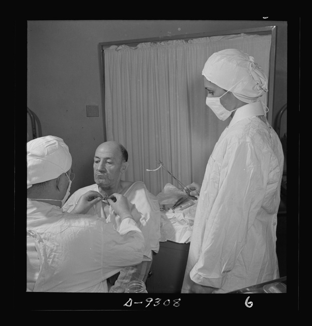 Nurse training. A student nurse stands by ready to assist the doctor as he changes a metal tube in a patient's throat (patient is suffering from inflammation of trachea caused by diptheria or other diseases)